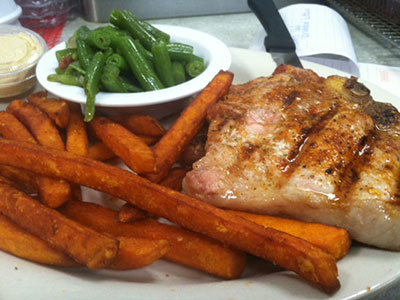 Hot, grilled pork chop with a side of sweet potato fries